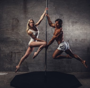 Couple in air on a pole dance stand.