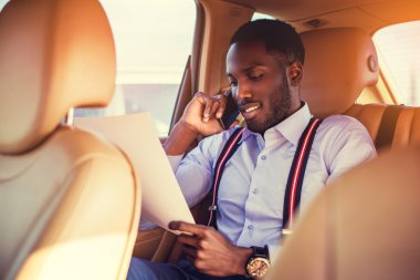 African man talking by smartphone in a car
