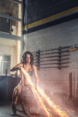 female exercising with burning battle rope