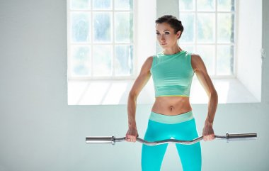 Female in azure sportswear holding barbell