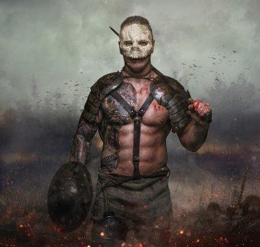 Male in the skull mask holds sword
