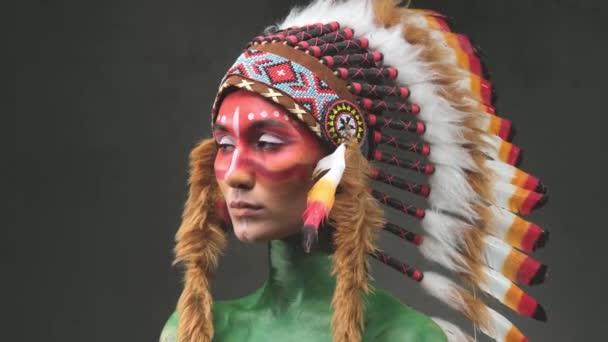 Gyönyörű nő viselt törzsi indián fejdísz pózol a sötét háttérben