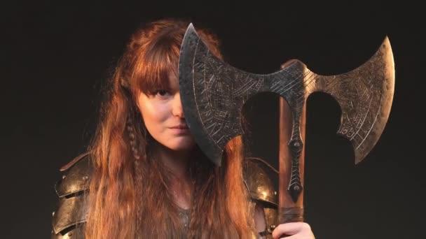 Vážné nordic žena barbar pózuje v tmavém pozadí drží sekeru v tmavém pozadí