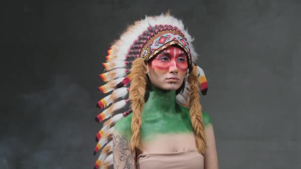 Beautiful woman weared with tribal indian headdress posing in dark smokey background