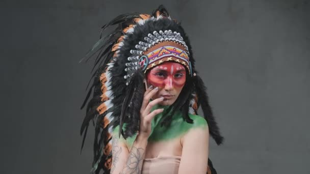 Tattooed female model poses with indian headdress in dark background