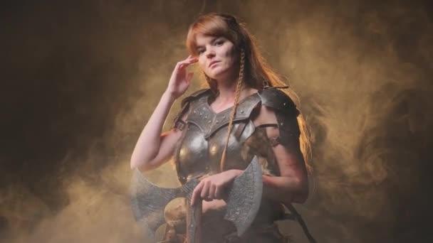 Jemná a krásná žena bojovník pózování v smokey pozadí se sekerou
