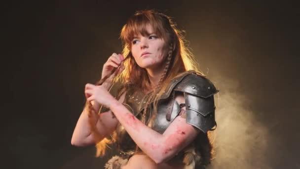 Žena severní bojovník v ocelové zbroji váže její dlouhé krásné hnědé vlasy v kouřovém pozadí