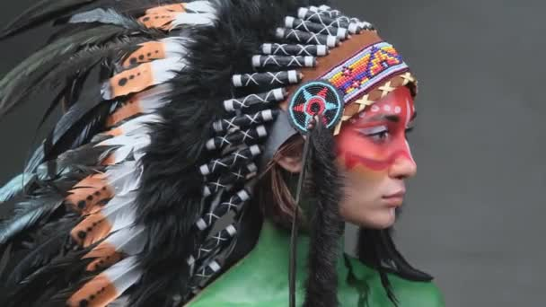 Női modell festett bőr és indiai fejdísz pózol sötét háttér