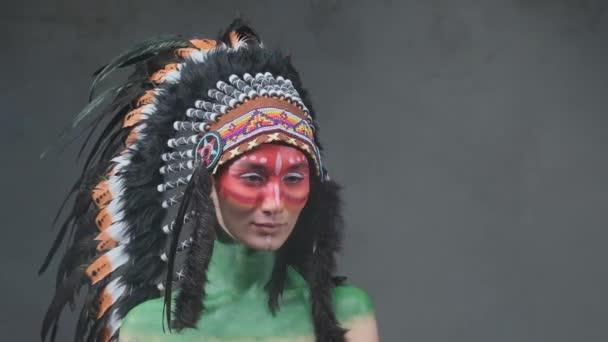 Vidám nő törzsi indián fejdísszel sötét füstös háttérben