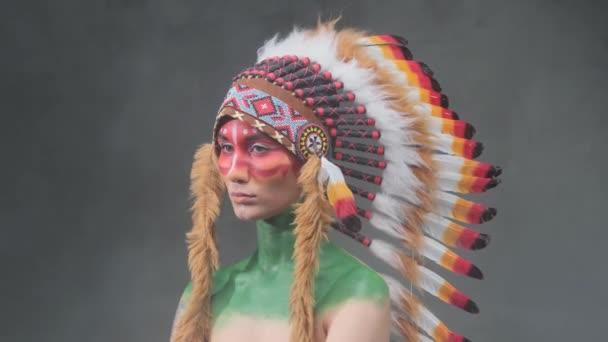 Gyönyörű nő viselt törzsi indián fejdísz pózol sötét füstös háttér