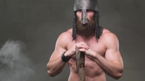 Nord bojovník pózování se sekerou a helmou v kouřovém pozadí