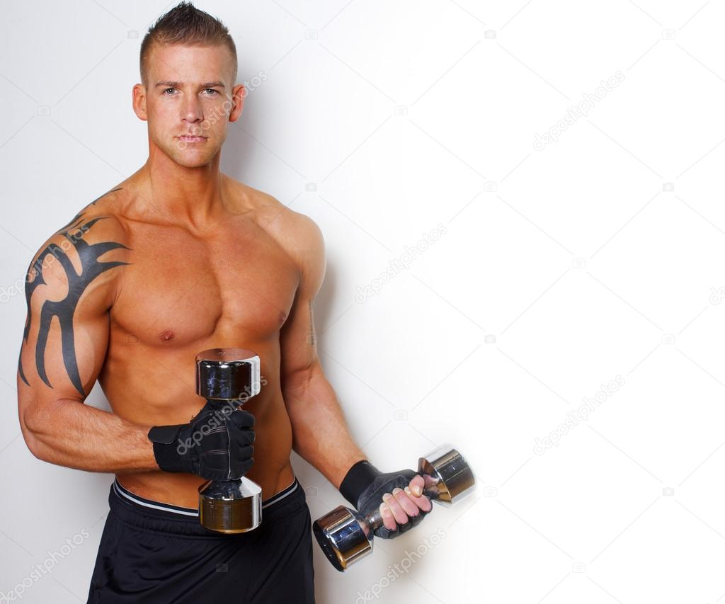 Hot guy with well looking body is holding dumbbells