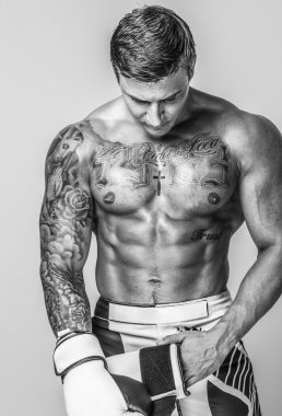 A muscled and tattooed man is putting on boxing gloves