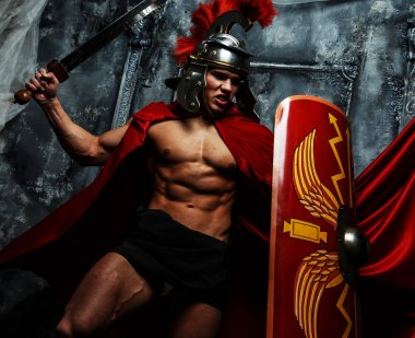 Muscular Roman posing on grey background.
