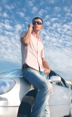 Handsome man calling by cellular phone near his car