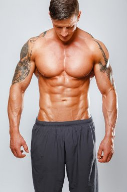 Muscular man poses showing his body