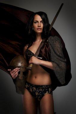 Goregeous female warrior poses holding sword and helmet