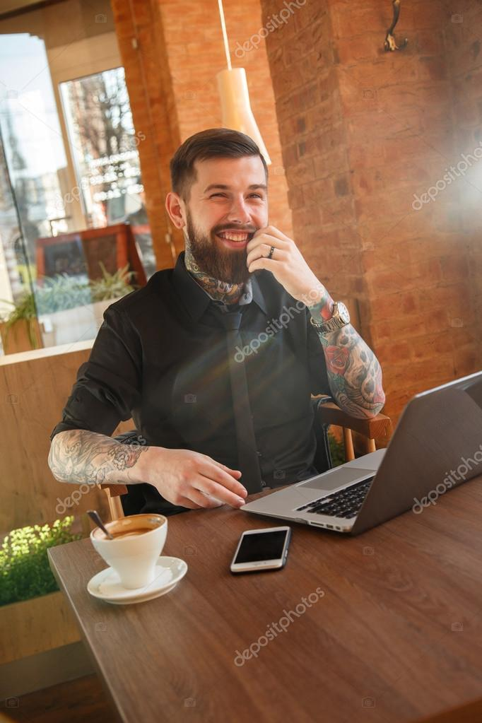 Faschionable man smiling sitting in coffee shop