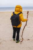 Photo Man in yellow jacket stands on the beach.