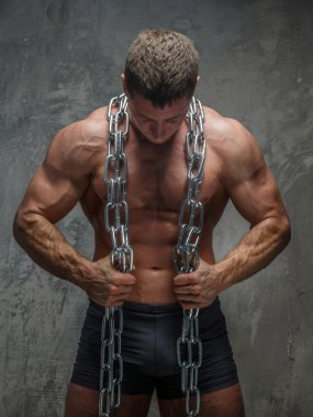 Big bodybuilder showing his body and holding steel chain