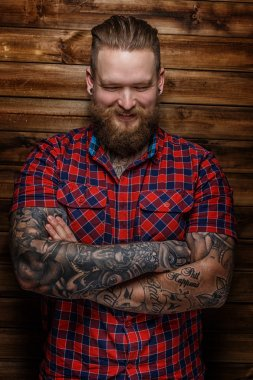 Brutal huge male with beard and tattooes with smile on his face