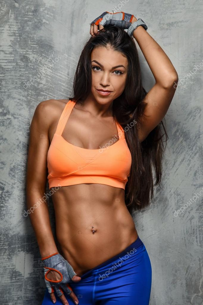 Attractive fitness woman posing in studio