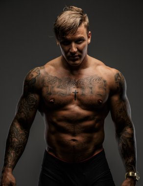 Tattooed muscular guy posing on gray background