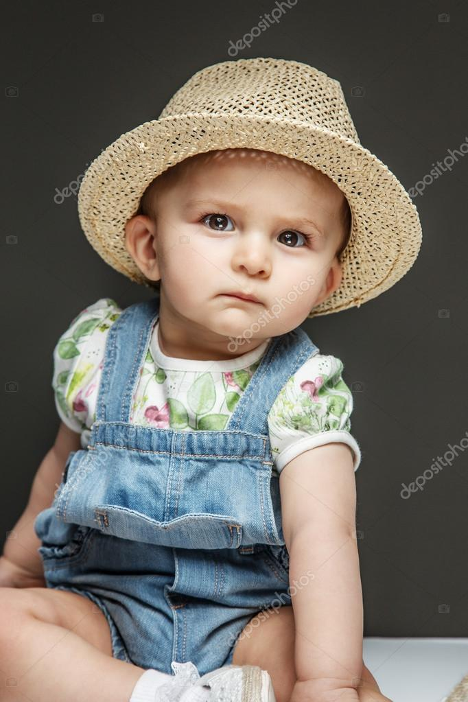 00a246ac001 Beautiful child in jeans dress an summer hat on grey background — Photo by  ...