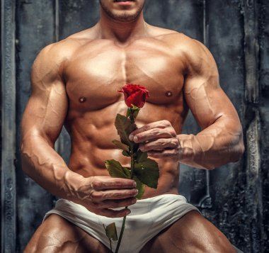 Muscular male in white pantie holding red rose.