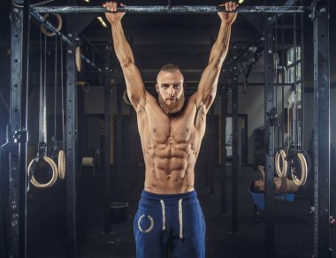 Shirtless muscular man in blue sports pants.