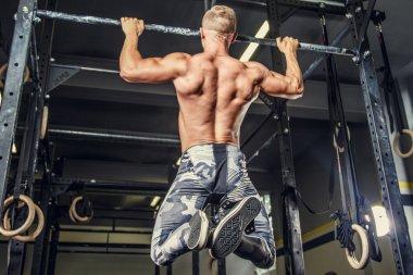 Shirtless man pulling up on horizontal bar.