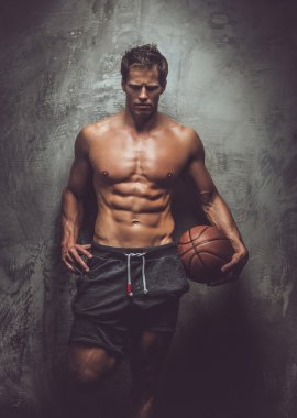 Muscular male in grey shorts holding basket ball.