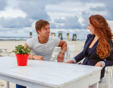 Redhead woman talking to young guy.