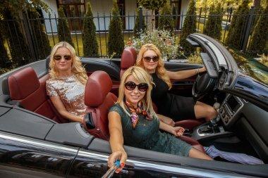 Three  girls in sunglasses posing in a car.