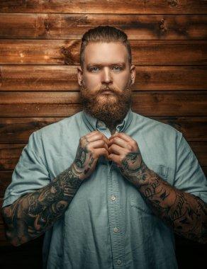 Brutal man with beard and tatoos.