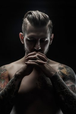 Portrait of shirtless man with tatooed body.