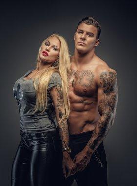 Blond woman posing with shirtless man.