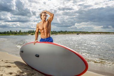 Handsome muscular man holding surfboard.