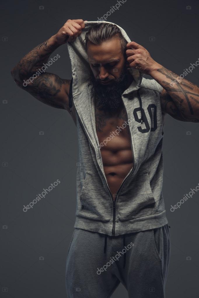 Brutal tattooed man in grey hoodie.