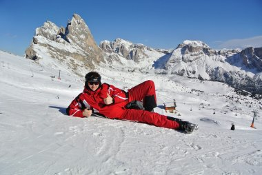 Skier in red coustume lying on snow.