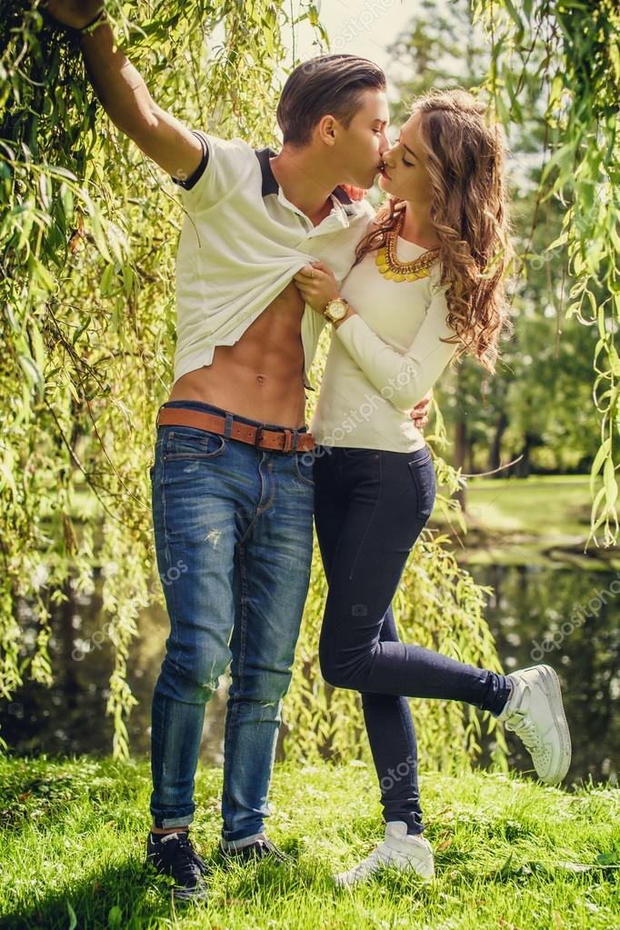 Young couple posing under tree.