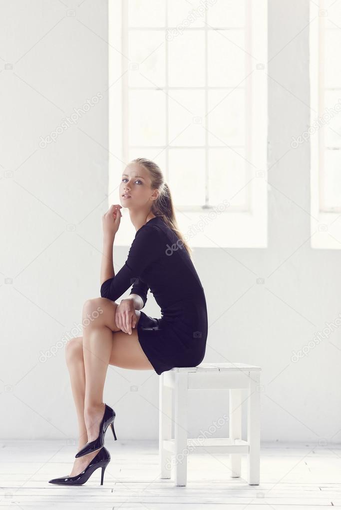 3844ae8d6570 Λεπτή γυναίκα σε ένα μαύρο κοντό φόρεμα που κάθεται σε μια καρέκλα σε ένα  λευκό δωμάτιο — Εικόνα από fxquadro
