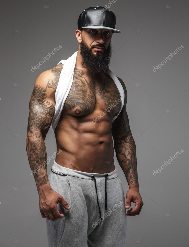 dffd3e9ef Bearded man with muscular tattooed body standing on a grey background.