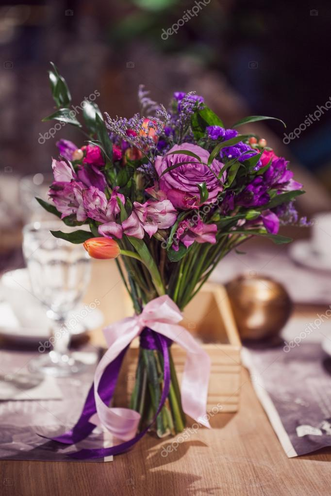 Flowers composition in restaurant,  roses and irises, combination shades of purple