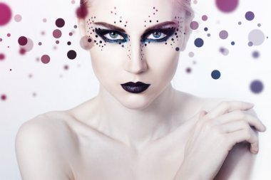 Beauty Fashion Model Girl with smoky eyes and black lips. Dots background