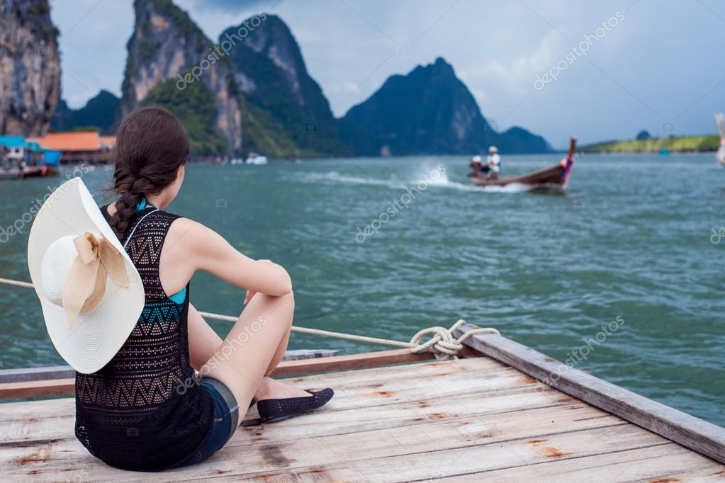 Girl in hat sitting on pier and enjoy view. Young woman in Thailand, back.