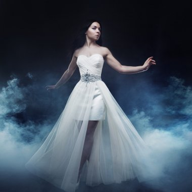 Beautiful sexy young woman. Portrait of girl in long white dress, mystical, mysterious style, dark background