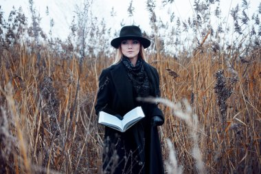 Portrait of young attractive woman in black coat and hat. Shes one in a field reading book, autumn landscape, dry grass