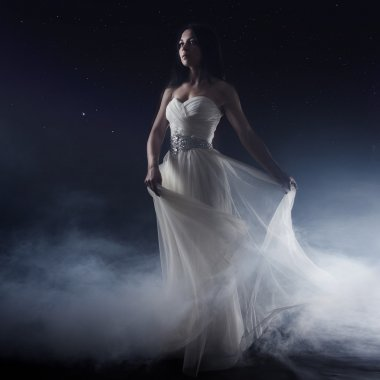 Beautiful sexy young woman. Portrait of girl in long white dress, mystical, mysterious style, background of the starry sky