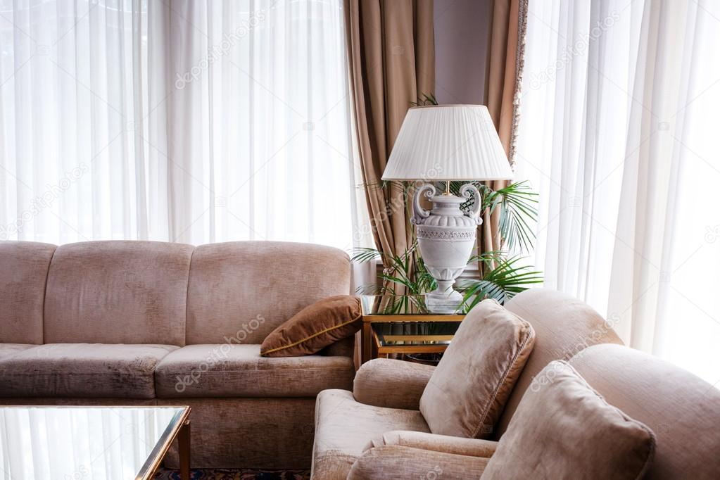 Living room interior in warm tones. Two leather sofas with cushions, lamp on the table